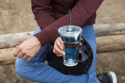 Mockup of a Tumbler with a Straw Held by a Man at a Park 24437
