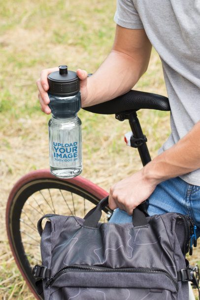 Mockup of a Water Bottle in the Hand of a Man Sitting on His Bike 24431