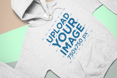 Mockup of a Heathered Pullover Hoodie Laid Flat on a Tricolor Surface 24541