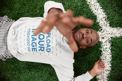 Sweatshirt Mockup of a Cool Man Reaching for the Camera Lying on Grass 21688