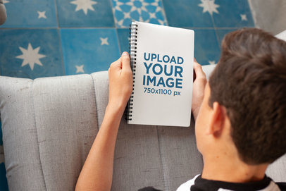 Mockup of a Boy Looking at His Notebook 24138