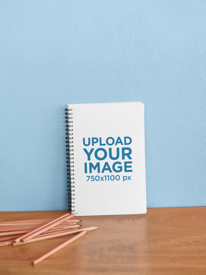 Mockup of a Spiral Notebook Leaning on a Wall 24175