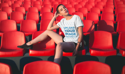 T-Shirt Mockup of a Short-Haired Girl Sitting in a Stadium with Red Seats 20182