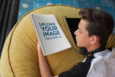 Notebook Mockup Featuring a Young Boy at Home looking at a Spiral Notebook Cover 24142