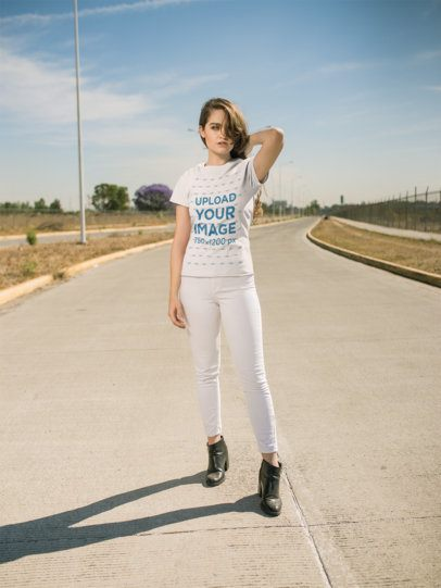 Mockup of a Woman in White Jeans and a Tshirt Posing on an Empty Road 20077
