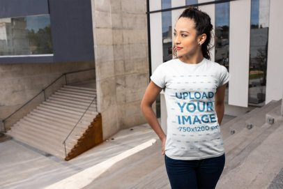 Mockup of a Woman Wearing a Tee in Front of a City Building 24664