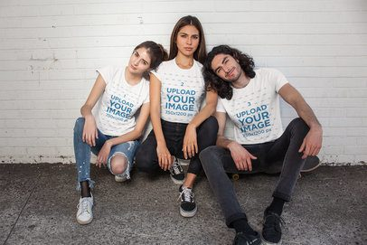 Mockup of Three Friends Wearing T-Shirts Crouching Against a Wall 25221