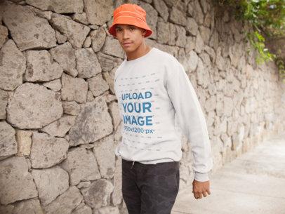 Crewneck Sweatshirt Mockup of a Man Walking by a Stone Wall 21062