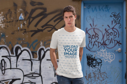 T-Shirt Mockup of a Man Standing by a Graffiti Art Wall 25299