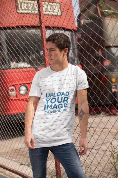 Mockup of a Man Wearing a Tee in Front of an English Style Bus 25297