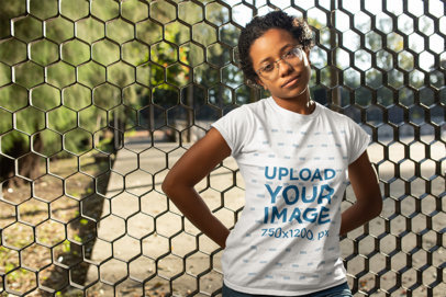 T-Shirt Mockup of a Curly Haired Woman Leaning on a Fence 24102