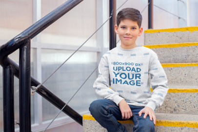 Sweatshirt Mockup Featuring a Young Boy Sitting by the Stairs 24841