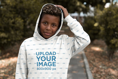 Mockup of a Young Boy Wearing a Sublimated Hoodie in a Park 24941