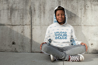 Hoodie Mockup Featuring a Young Boy Sitting Happily 24939