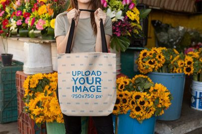 Tote Bag Mockup of a Girl Standing Against Buckets Full of Flowers 24872