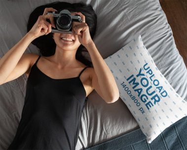 Pillow Mockup Featuring a Woman Taking a Photo with a Retro Camera 25920