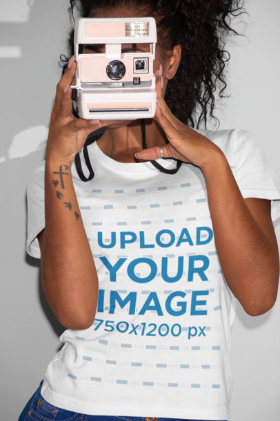 T-Shirt Mockup Featuring a Woman Taking a Picture with a Polaroid Camera 21902