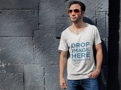 T-Shirt Mockup of a Young Man Leaning on a Stone Wall 6495a