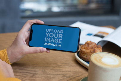 Mockup of an iPhone XS Being Held on Landscape Position Over a Cafe Table 25372
