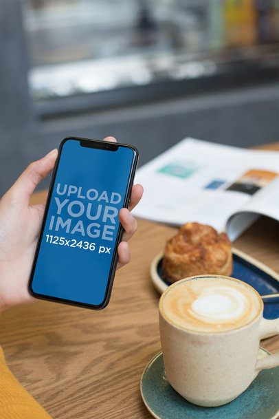 Mockup of a Woman Holding an iPhone XS While at a Cafe 25371