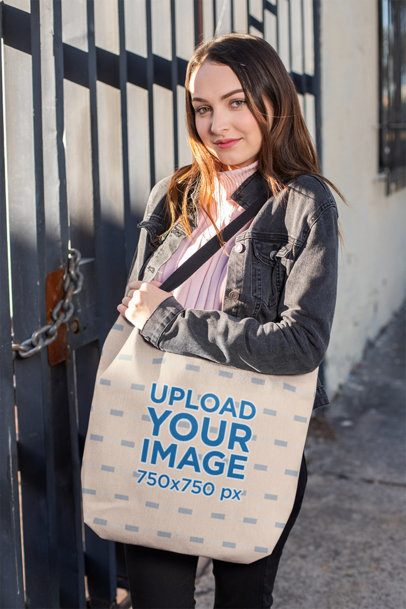 Mockup Featuring a Girl Showing her Tote Bag on the Street 24881