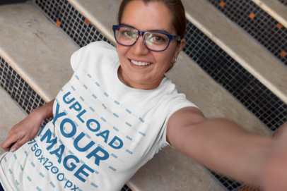 T-Shirt Mockup of a Happy Customer with Glasses Taking a Selfie on the Stairs 26197
