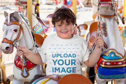 Mockup of a Kid Wearing a Plus Size T-Shirt While Riding a Carousel 25548