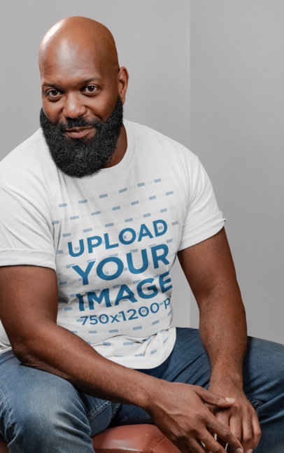 T-Shirt Mockup of a Bald Bearded Man Sitting on a Chair 21526