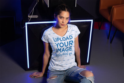 V-Neck T-Shirt Mockup Featuring a Girl Sitting in a Room with Neon Lights 24925