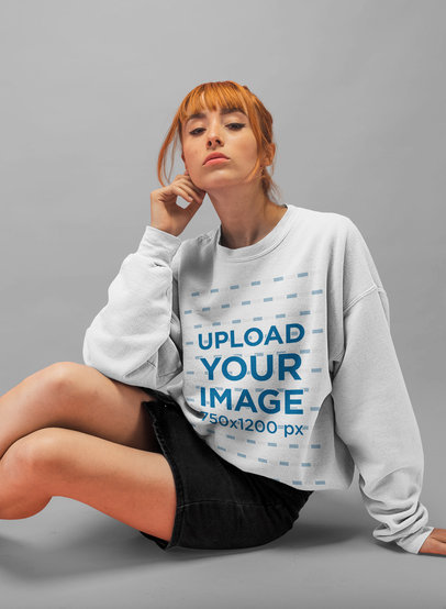 Baggy Sweatshirt Mockup of a Girl with Red Hair Bangs Sitting Seductively in a Studio 20881