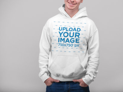 Mockup of a Smirking Man Wearing a Hoodie at a Photo Studio 23084