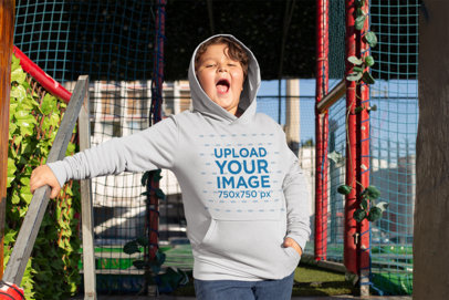 Plus Size Pullover Hoodie Mockup of a Joyful Kid Outside a Caged Turf Field 25563