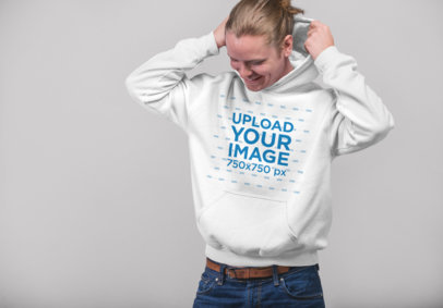 Mockup of a Blonde Man Putting on His Pull-Over Hoodie in a Studio 23085