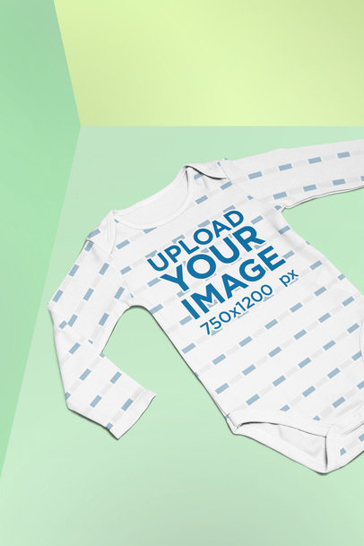 Mockup of a Sublimated Baby Onesie Lying on a Split Colored Background 25171