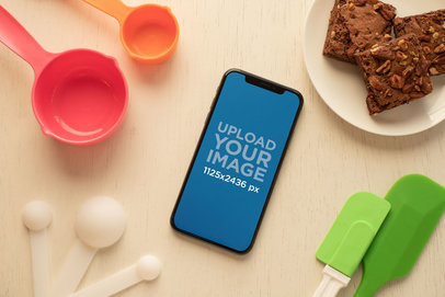 Mockup of an iPhone XS Surrounded by Baking Supplies 25490