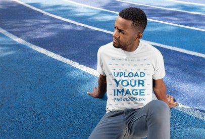 T-Shirt Mockup of a Man Sitting on a Blue Track 25924