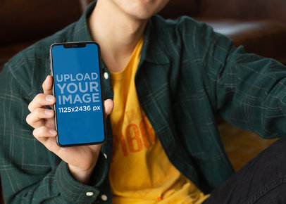 Mockup of a Slim Man Holding an iPhone X 25546