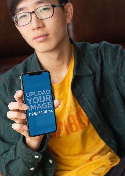 Mockup of a Geeky Looking Man Showing Off His iPhone X 25545