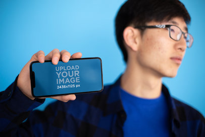 iPhone X Mockup of a Man with Glasses Looking Away 25540