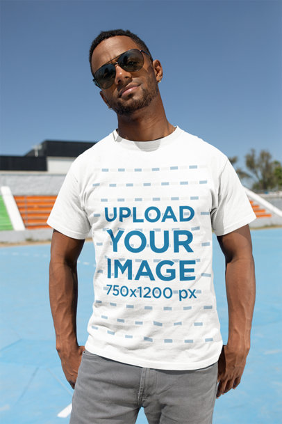 T-Shirt Mockup of a Muscled Man Wearing Sunglasses in a Sports Field 25933