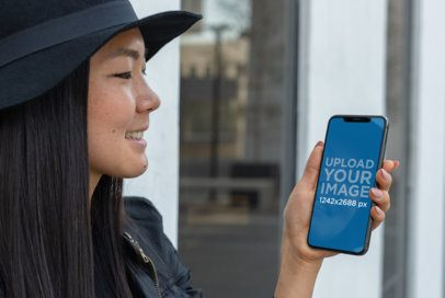 Mockup of a Smiling Girl with a Hat Holding Her iPhone XS Max in an Urban Scenario 25771
