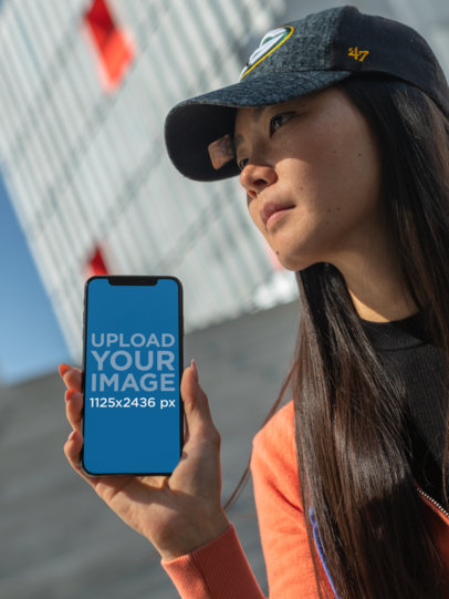 iPhone XS Mockup of a Long-Haired Girl with a Cap Staring into the Sky 25775