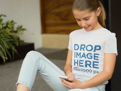 T-Shirt Mockup Featuring a Girl Using an iPhone 6 a7938