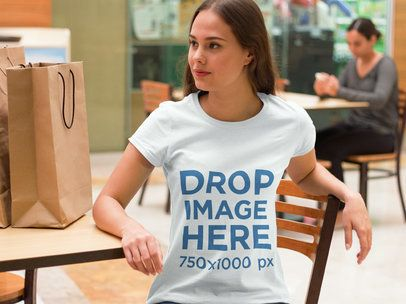 T-Shirt Mockup of a Woman Sitting in a Mall Food Court a7983