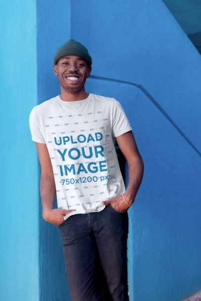 T-Shirt Mockup of a Smiling Man with a Beanie Casually Posing by a Blue Wall 26313