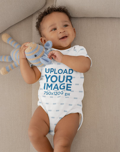 Onesie Mockup Featuring a Joyful Baby Boy Grabbing His Stuffed Toy 25123