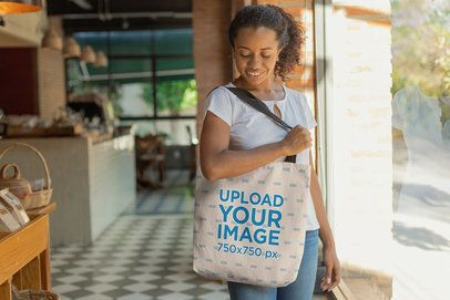 Mockup of a Kinky-Haired Woman Carrying a Tote Bag on Her Shoulder at a Food Market 26698