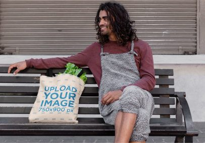 Tote Bag Mockup of a Long-Haired Man Sitting on a Bench 26704