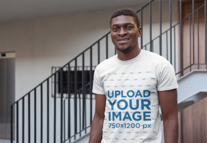 Mockup of a Smiling Man Wearing a T-Shirt Next to a Staircase 26623