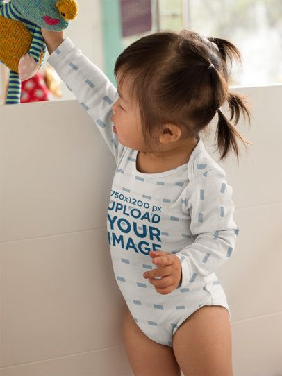 Onesie Mockup of a Cute Baby Playing with Her Rag Doll 25129